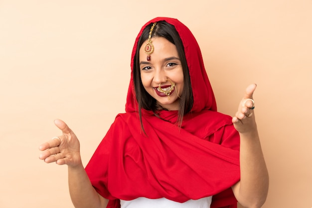Young indian woman isolated on beige space presenting and inviting to come with hand