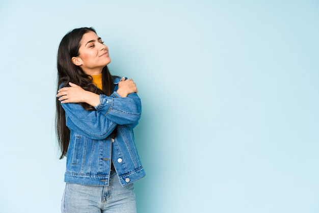 Young indian woman isolated on blue background hugs, smiling carefree and happy.