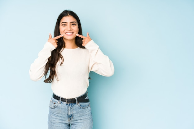 Young indian woman isolated on blue background smiles, pointing fingers at mouth.