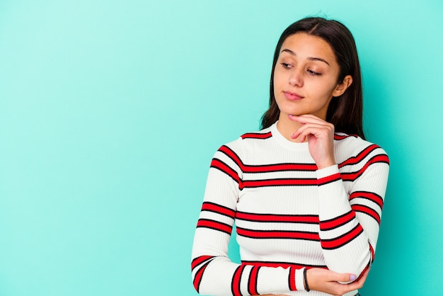 Young indian woman isolated on blue wall looking sideways with doubtful and skeptical expression.