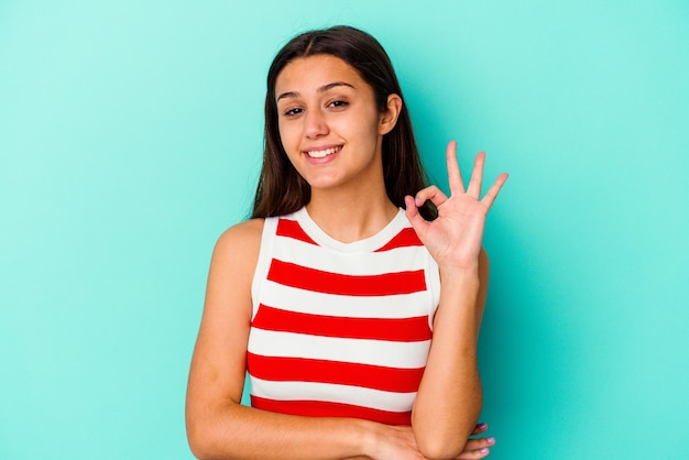 Young indian woman isolated on blue winks an eye and holds an okay gesture with hand.