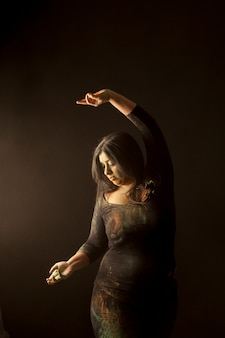Young indian woman isolated dancing and playing with colored dust in dark clothes