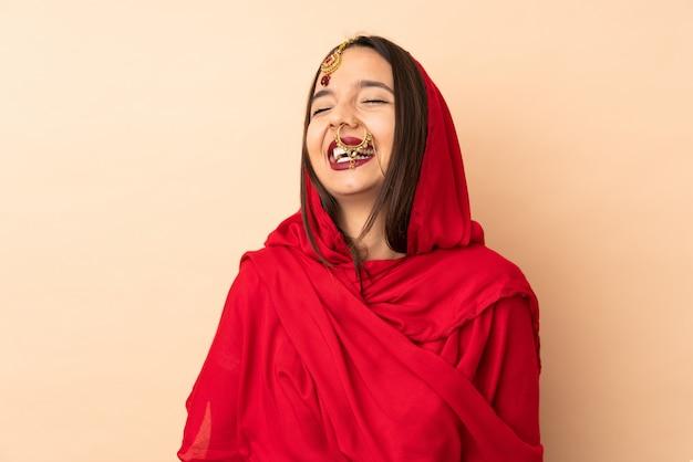 笑ってベージュ色の背景上に分離されて若いインド人女性