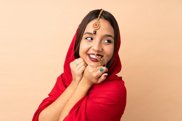 ベージュ色の背景に分離された若いインド人女性
