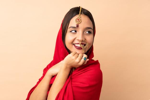 ベージュの背景に分離された若いインド人女性