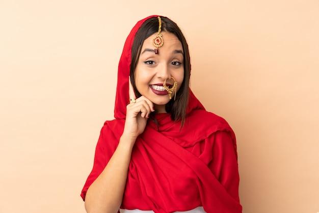ベージュの笑いに分離された若いインド人女性