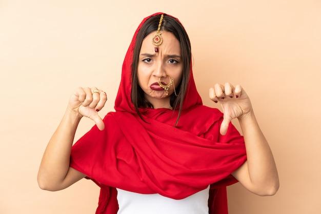 Молодая индийская женщина, изолированные на бежевом, показывая пальцем вниз двумя руками