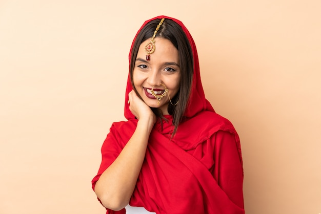 ベージュの空間が笑いに分離された若いインド人女性