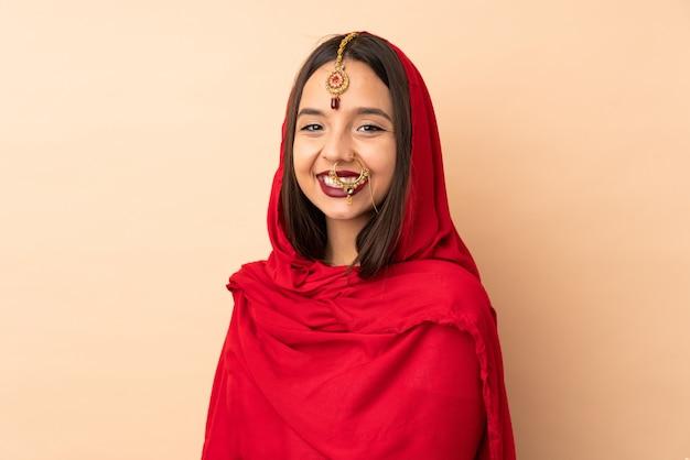 ベージュの空間に分離された若いインド人女性