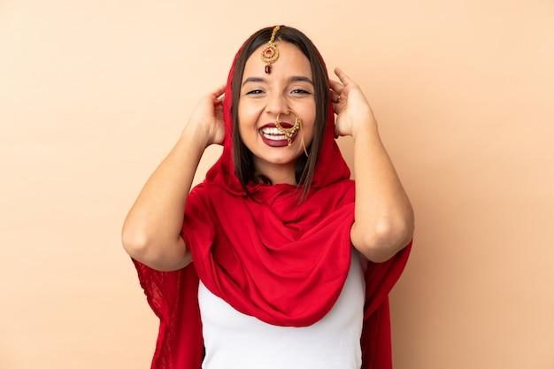 ベージュの壁が笑いに分離された若いインド人女性