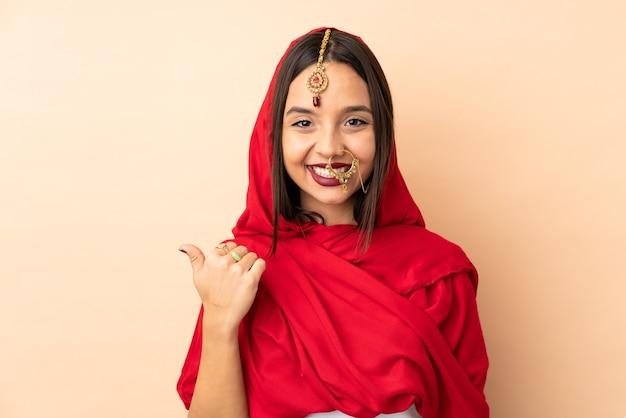 Молодая индийская женщина изолирована на бежевой стене, указывая в сторону, чтобы представить продукт