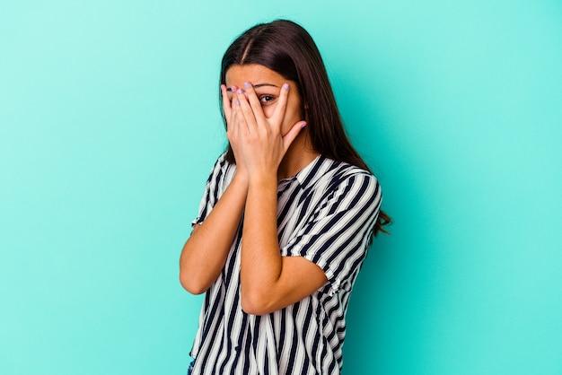 Молодая индийская женщина, изолированная на синем фоне, моргает сквозь пальцы испуганно и нервно.