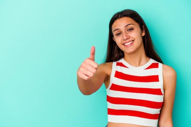 Молодая индийская женщина, изолированная на синем фоне, улыбается и поднимает палец вверх