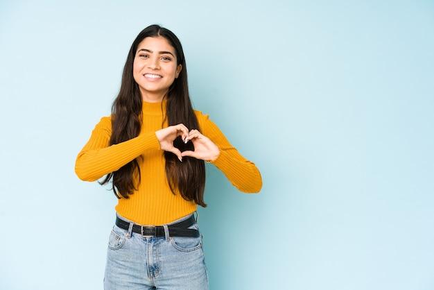 Молодая индийская женщина, изолированных на синем фоне улыбается и показывает форму сердца руками.