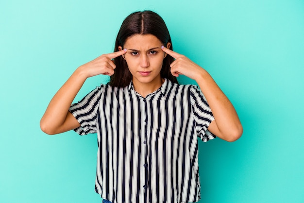 Молодая индийская женщина, изолированная на синем, сосредоточилась на задаче, держа указательные пальцы, указывая головой.