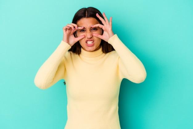 Молодая индийская женщина изолирована на синем, держа глаза открытыми, чтобы найти возможность успеха.