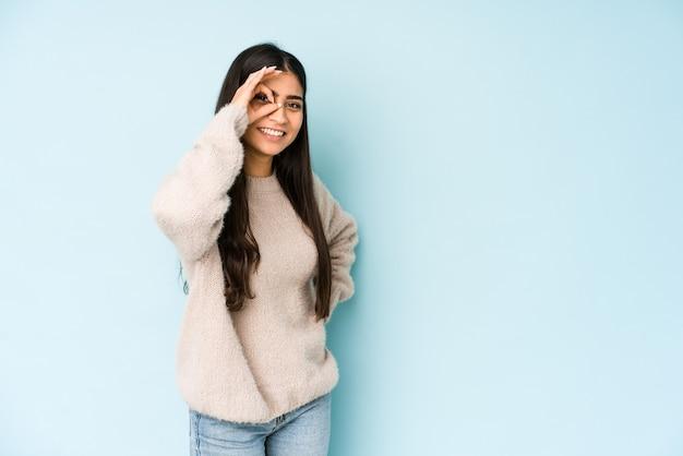 青い空間に孤立した若いインド人女性は、目で大丈夫なジェスチャーを維持して興奮しました。