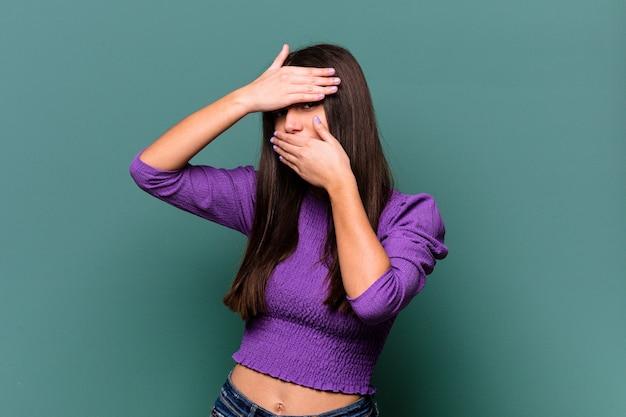 파란색 벽에 고립 된 젊은 인도 여자는 얼굴을 덮고 당황, 손가락을 통해 카메라에 깜박