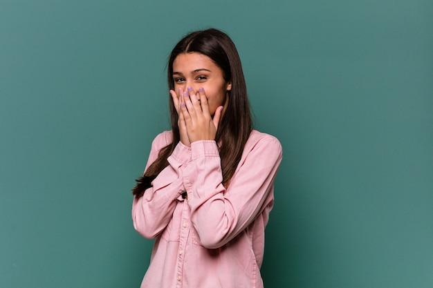 뭔가에 대해 웃고 파란색 벽에 고립 된 젊은 인도 여성, 손으로 입을 덮고