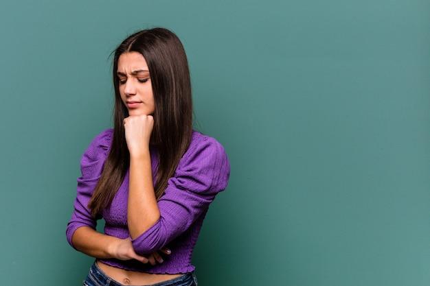 의심스럽고 회의적인 표정으로 옆으로보고 파란색 벽에 고립 된 젊은 인도 여자