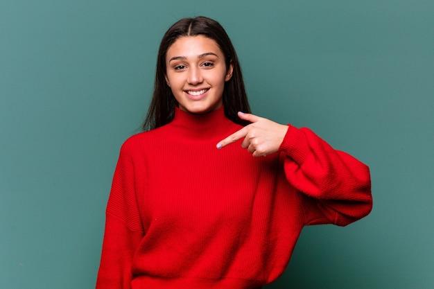 자랑스럽고 자신감, 셔츠 복사 공간을 손으로 가리키는 파란색 벽 사람에 고립 된 젊은 인도 여자