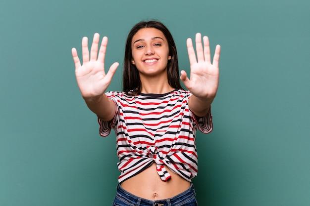손으로 번호 10을 보여주는 파란색 벽에 고립 된 젊은 인도 여자.