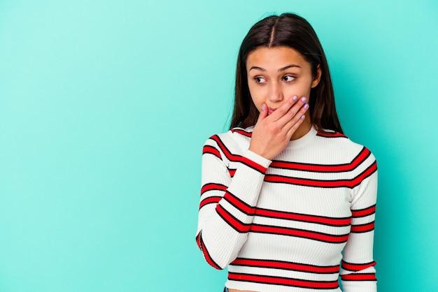 手で口を覆うコピースペースを思慮深く見て青い壁に孤立した若いインド人女性。