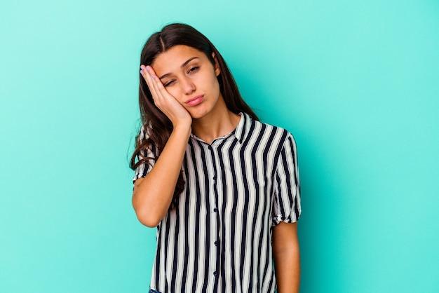 Молодая индийская женщина, изолированная на синей стене, устала и очень сонная, держа руку на голове.