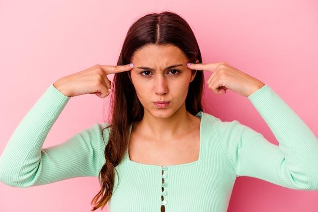 ピンクの背景に孤立した若いインド人女性は、人差し指を頭に向けたまま、タスクに焦点を当てました。