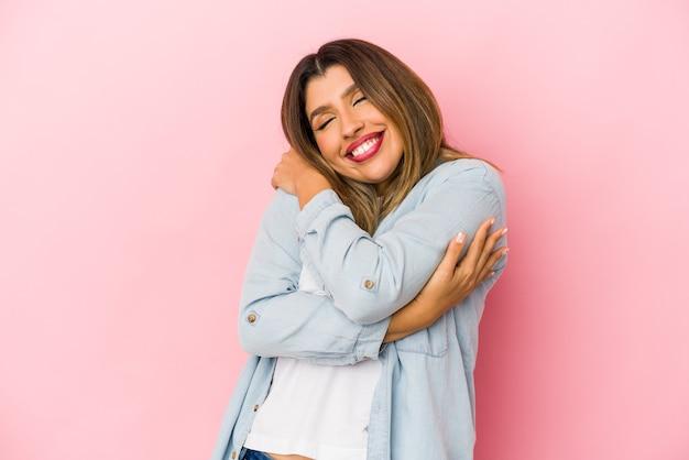 Молодая индийская женщина, изолированные на розовом фоне, обнимает, беззаботно улыбается и счастлива.