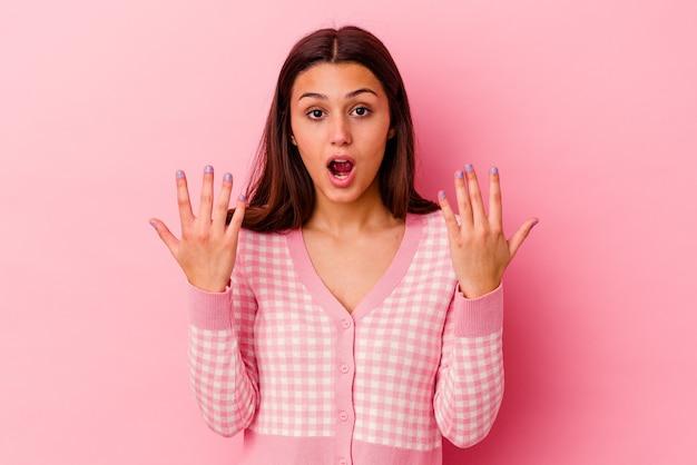 手で 10 番を示すピンクの背景に分離された若いインド人女性。