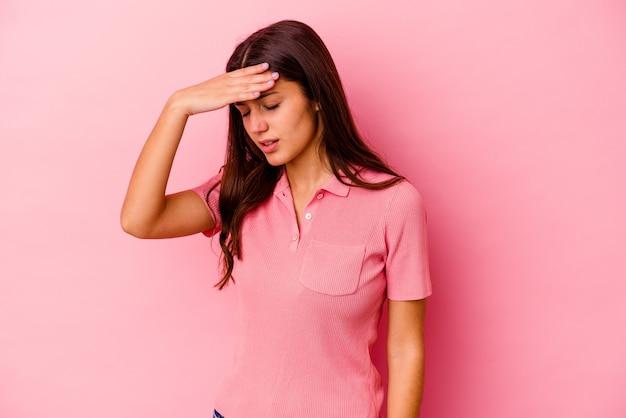 Молодая индийская женщина, изолированные на розовом фоне, трогательно виски и головная боль.