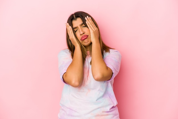 Молодая индийская женщина, изолированная на розовом фоне, плачет и плачет безутешно.