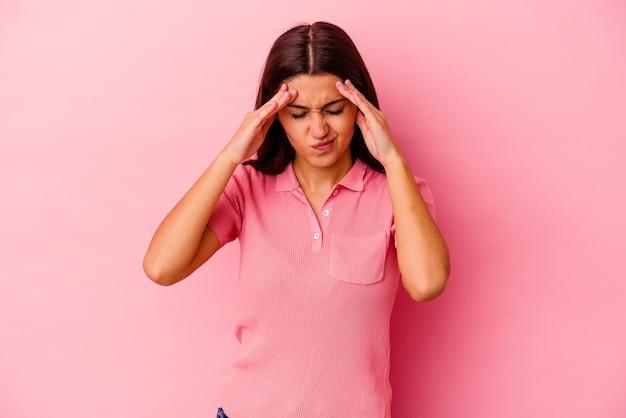 Молодая индийская женщина изолирована на розовом с головной болью, касаясь передней части лица.