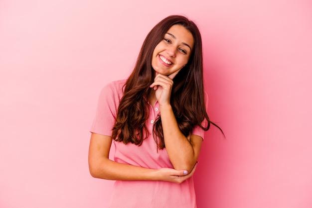 ピンクの笑顔で幸せで自信を持って、手で顎に触れて孤立した若いインド人女性。