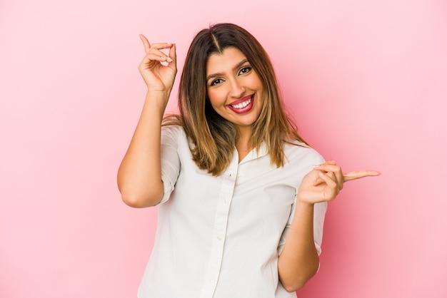 Молодая индийская женщина изолирована на розовой стене, указывая на разные места для копирования, выбирая одно из них, показывая пальцем.