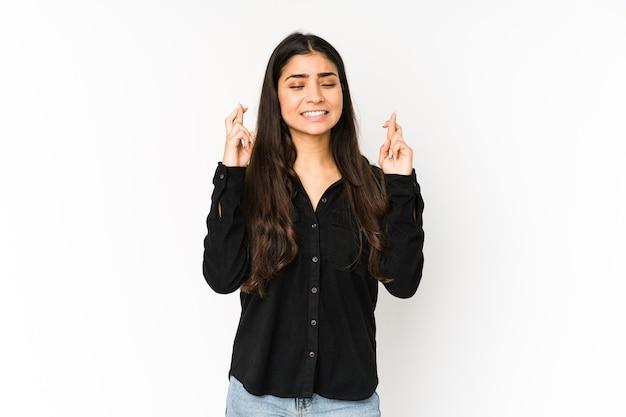 幸運を持っているために指を交差する紫色の背景に分離された若いインドの女性