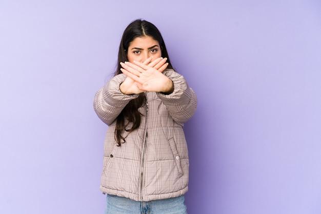 拒否ジェスチャーをしている紫色の背景に分離された若いインド人女性