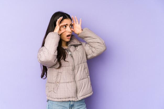 Молодая индийская женщина изолирована на фиолетовом фоне, держа глаза открытыми, чтобы найти возможность успеха.