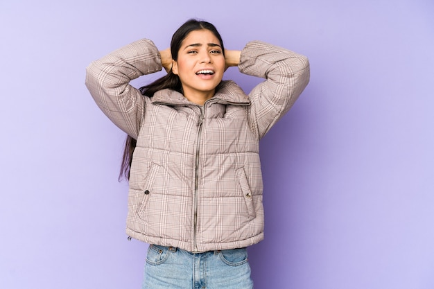 怒りで叫んで紫色の背景に分離された若いインド人女性。