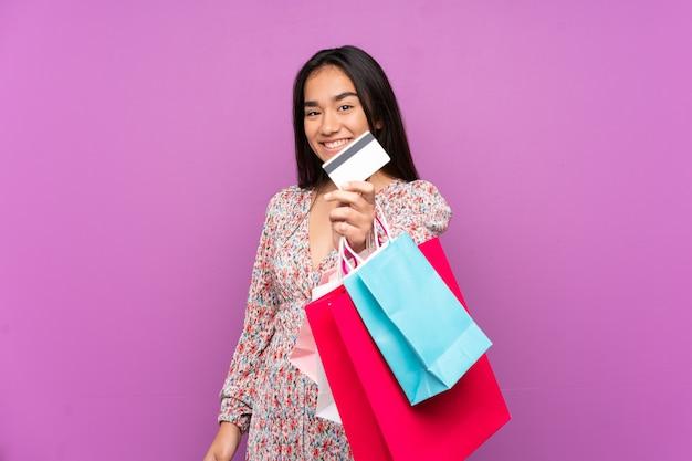 ショッピングバッグとクレジットカードを保持している紫色の若いインド人女性