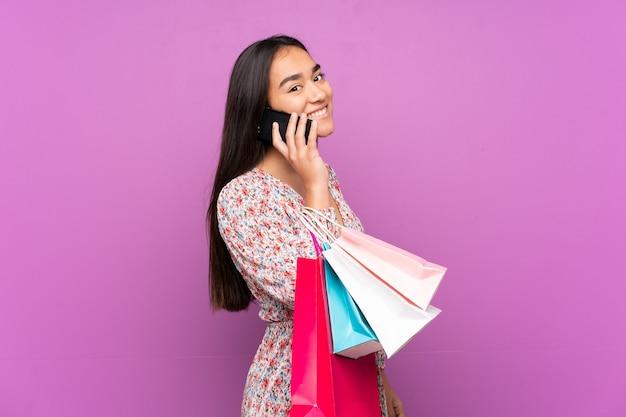 ショッピングバッグを持って、彼女の携帯電話で友人を呼び出す紫色に孤立した若いインドの女性