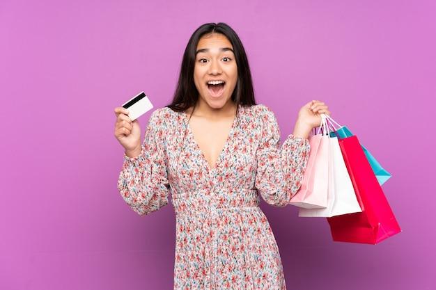 보라색 지주 쇼핑백에 고립 된 젊은 인도 여자와 놀