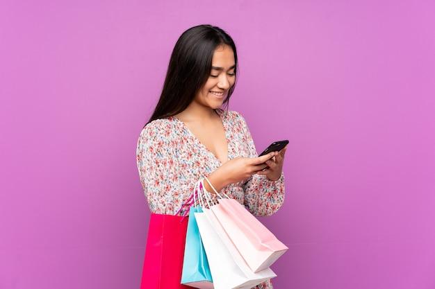 ショッピングバッグを持って、友人に彼女の携帯電話でメッセージを書いている紫色で孤立した若いインド人女性