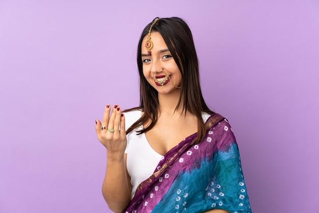 Молодая индийская женщина изолирована на фиолетовом, приглашая прийти с рукой. счастлив что ты пришел