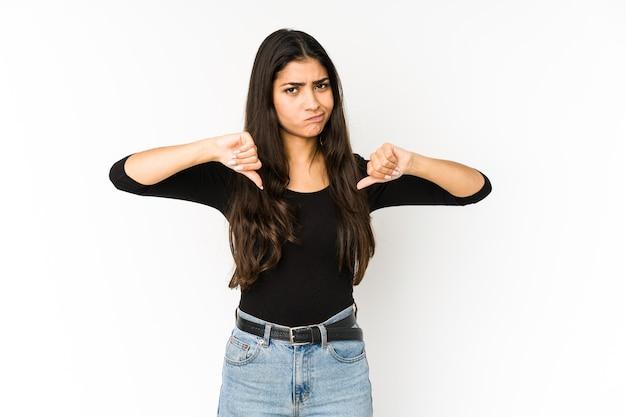 親指を下に、失望の概念を示す紫色に分離された若いインドの女性。