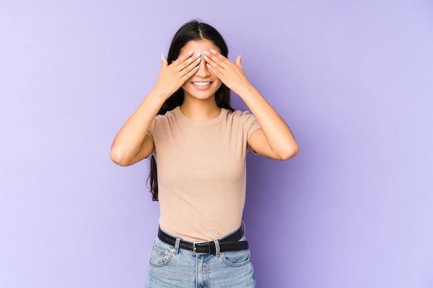 紫色の空間に孤立した若いインド人女性が目を覆い、驚きを広く待っている笑顔。