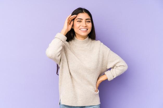 たくさん笑ってうれしそうな紫色の空間に孤立した若いインド人女性。幸福の概念。