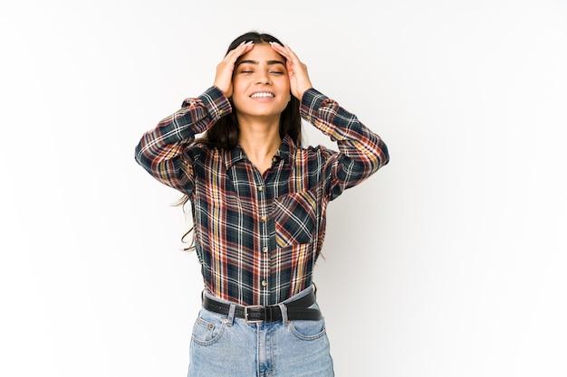 紫色の空間に孤立した若いインド人女性は、頭を抱えて喜んで笑います。幸福の概念。