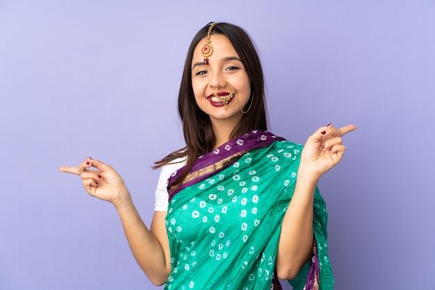 측면과 행복 보라색 공간을 가리키는 손가락에 고립 된 젊은 인도 여자